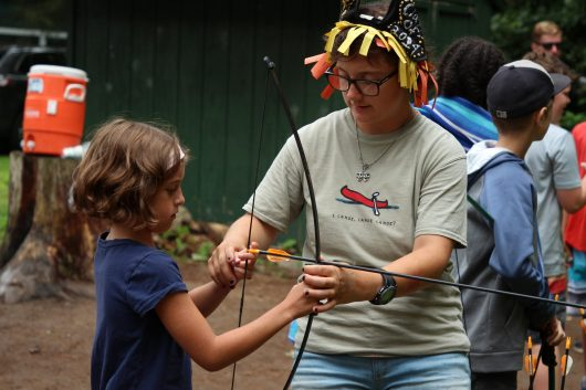 Lourdes camp employee helping a camper shoot a bow